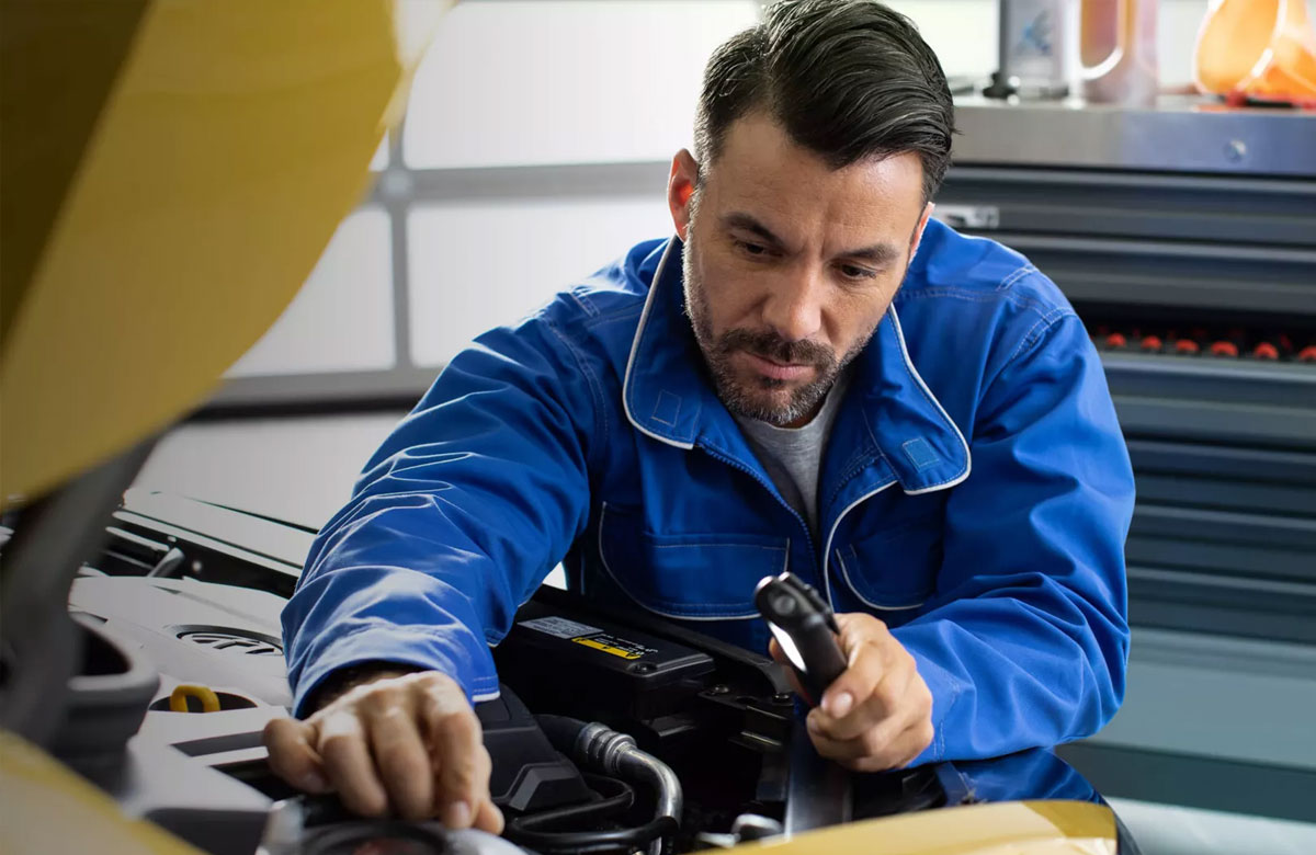 Mechanic in blue overalls working on car engine