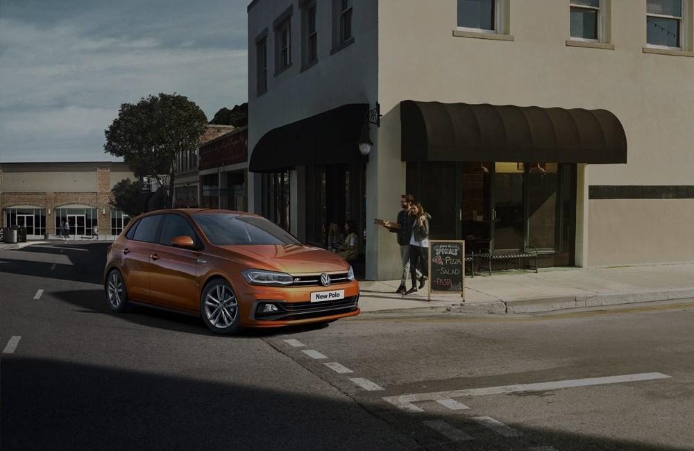Orange Volkswagen Polo turning street corner in town