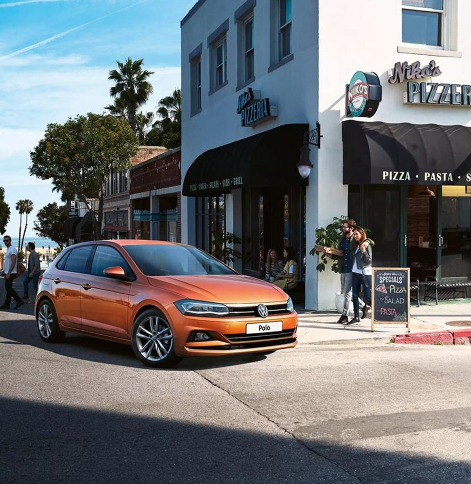 Orange Volkswagen Polo on street corner
