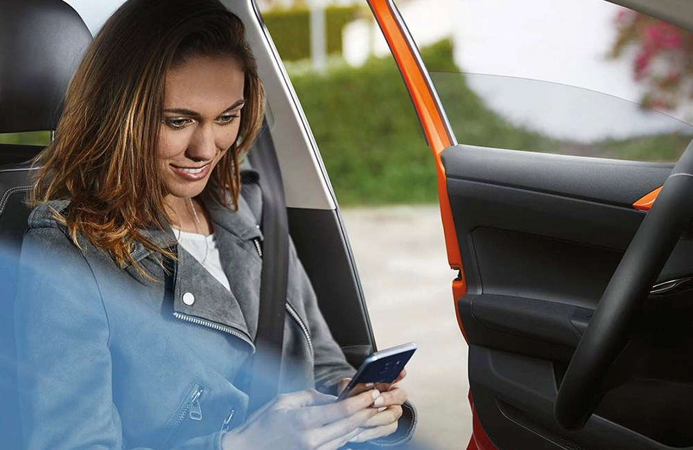 Woman looking at her phone in a car