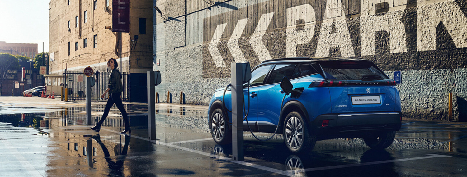 Blue Peugeot All-New 2008 SUV parked and plugged into charging station