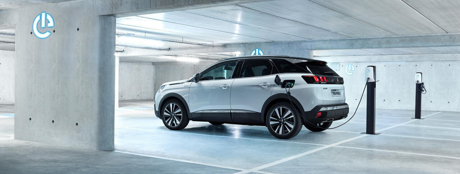 White Peugeot 3008 SUV Hybrid parked in underground car park and plugged in