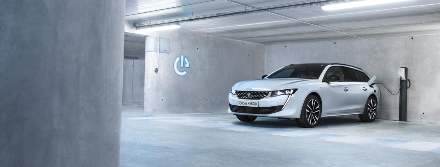 White Peugeot 508 SW Hybrid parked in underground car park and plugged in