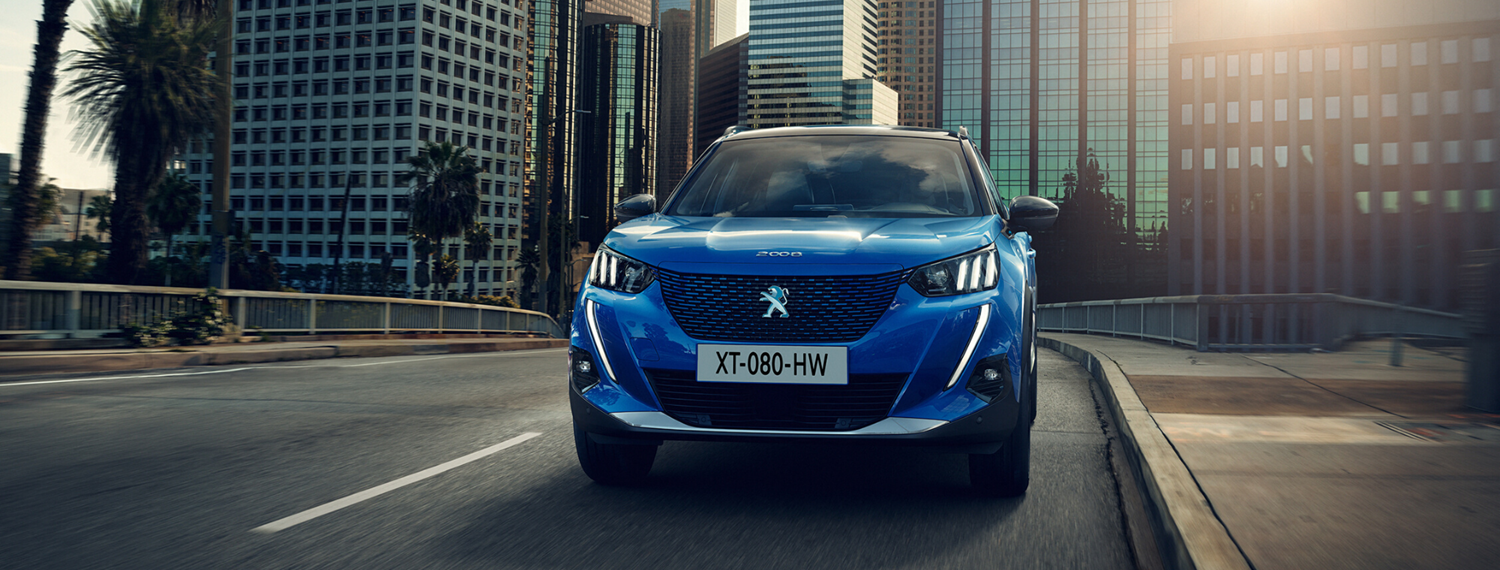 Front facing Blue All-New Peugeot 2008 SUV driving down road