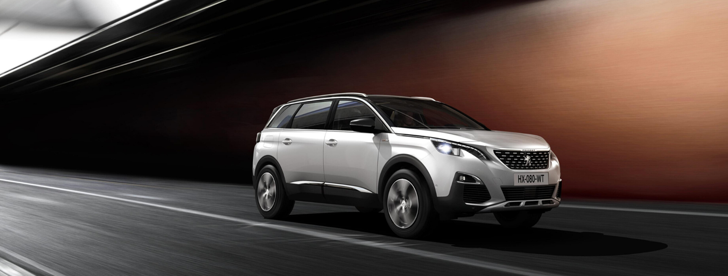 White Peugeot 5008 SUV driving on road