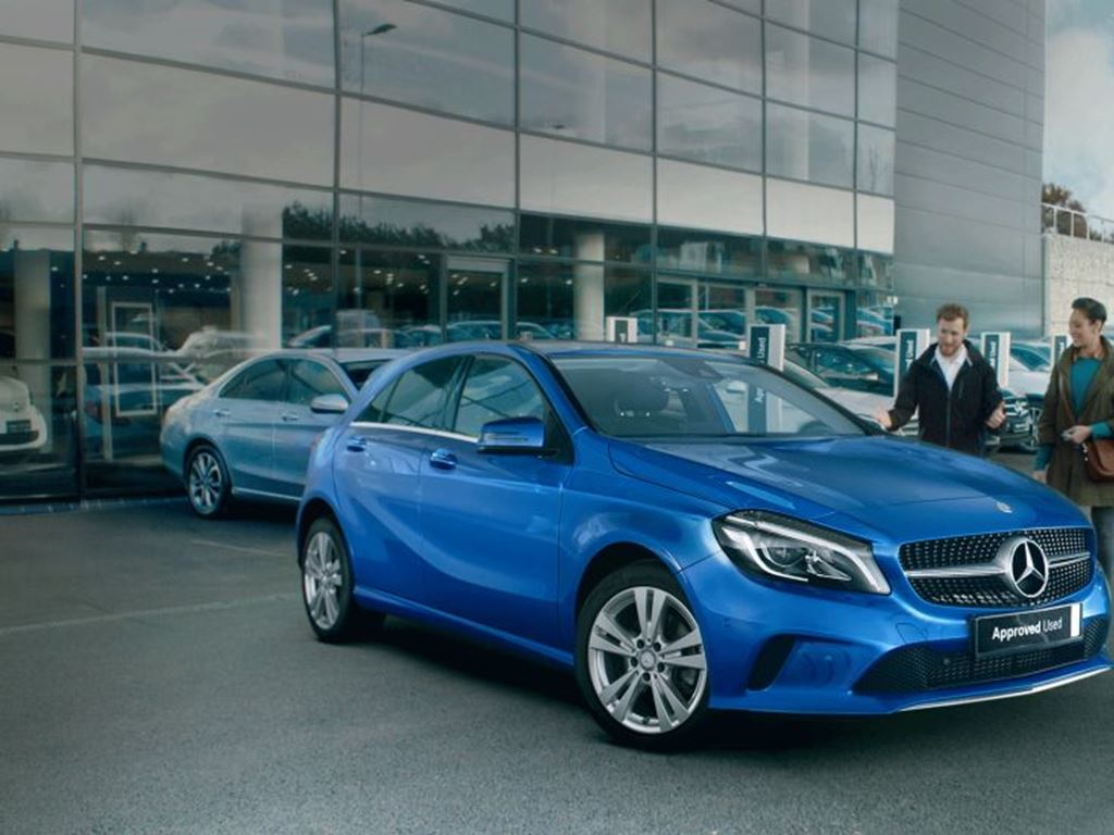 Two people stood by blue a-class