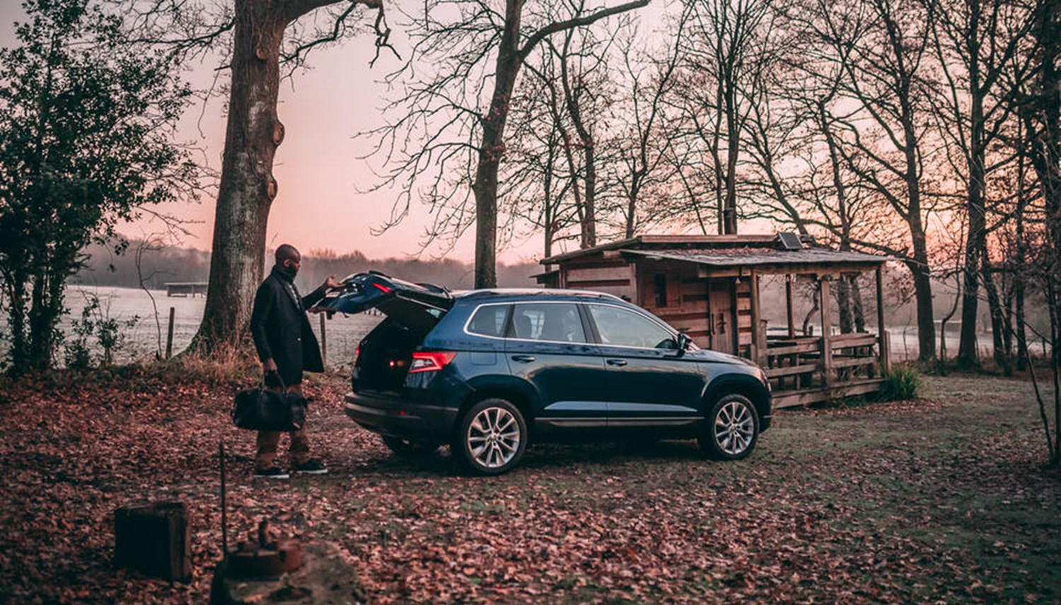 Skoda Karoq in blue in forest setting with wooden cabin and man opening boot
