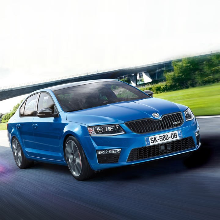 All new Octavia in blue riding along a road front view