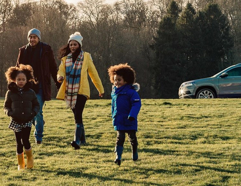 Family walking across a field away from a Skoda