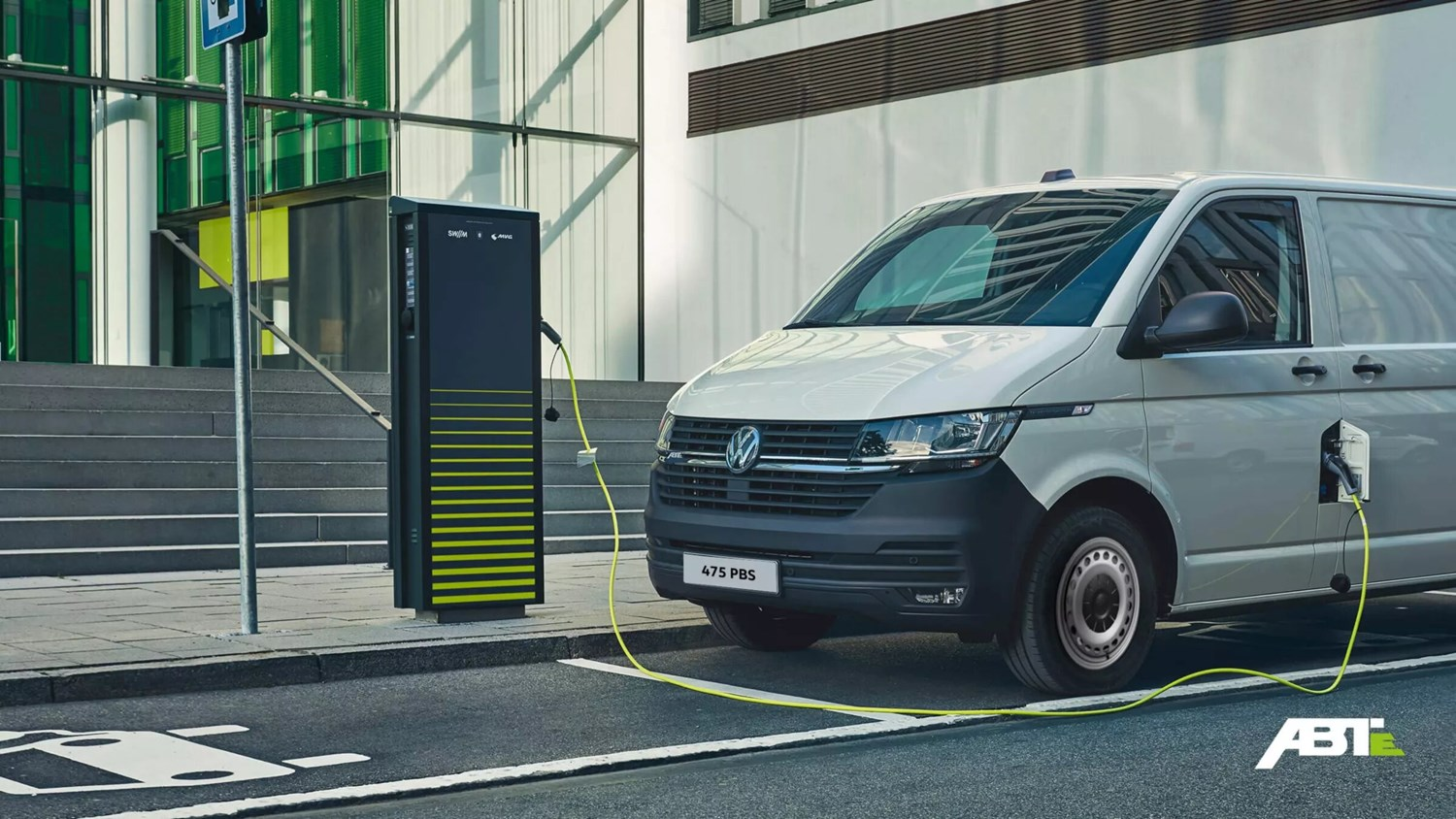 ABT e-Transporter plugged into a roadside charger in front of glass office building