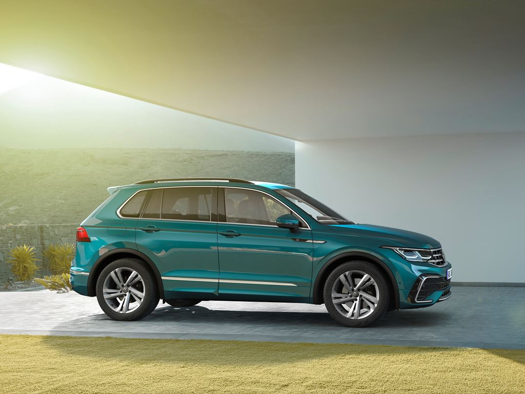 New Volkswagen Tiguan side view with lady walking towards the car