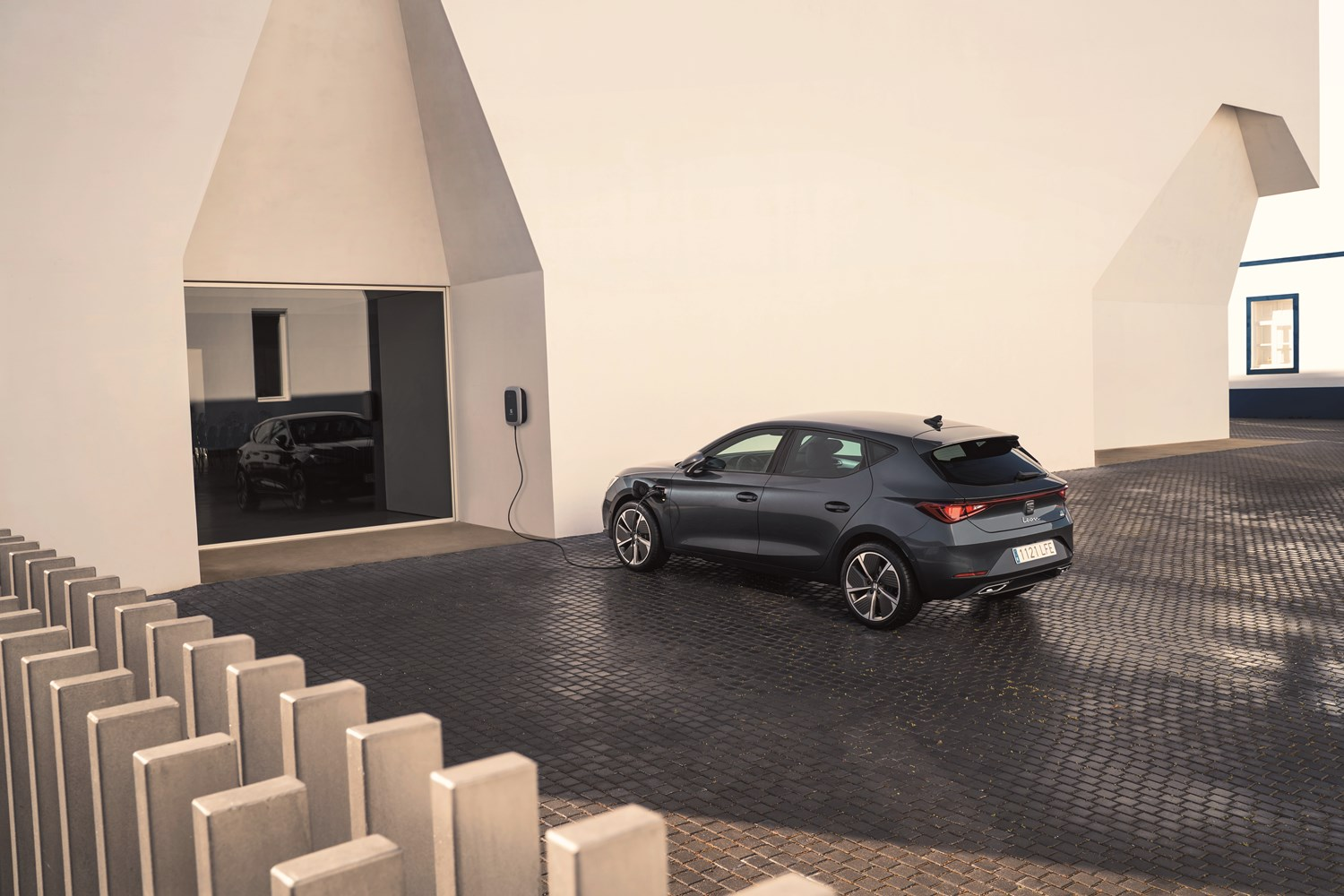 Seat Leon hybrid on block paving, plugged into wall charging point on a cream rendered wall near to a black door
