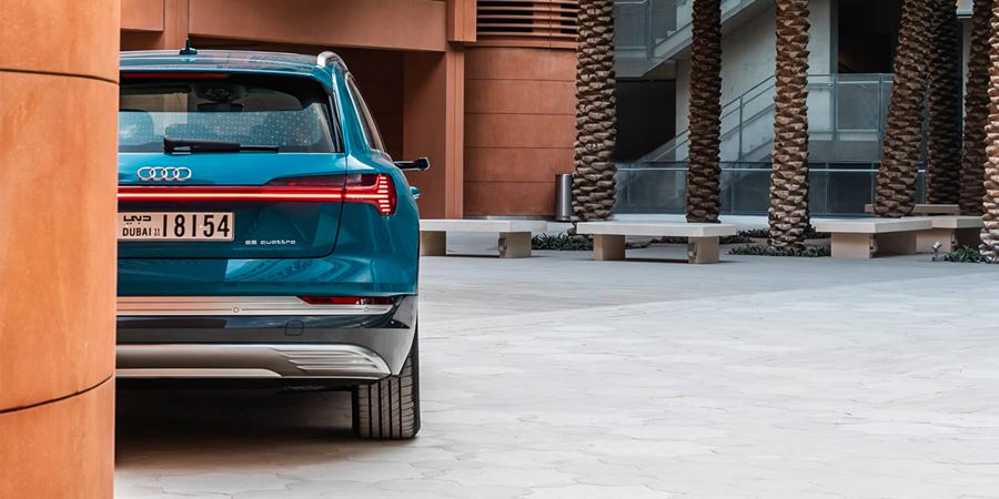 Rear of a blue e-tron with left hand side behing a wall. Background is orange walls and pillars with tree trunks and seating area to the right