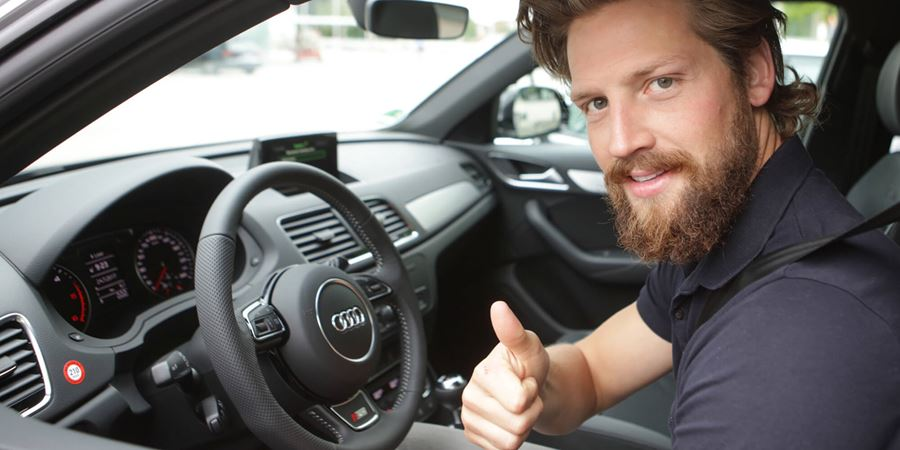 Man with brown hair and a brown beard wearing a blue polo shirt, with a thumbs up and a seat belt on, sat in the drivers seat of an audi