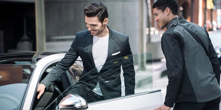 Man in a suit jacket with white t-shirt with short dark hair and stubble getting into a car. Another man with a jacket and bag over his shoulder with dark short hair holds the door of the car open