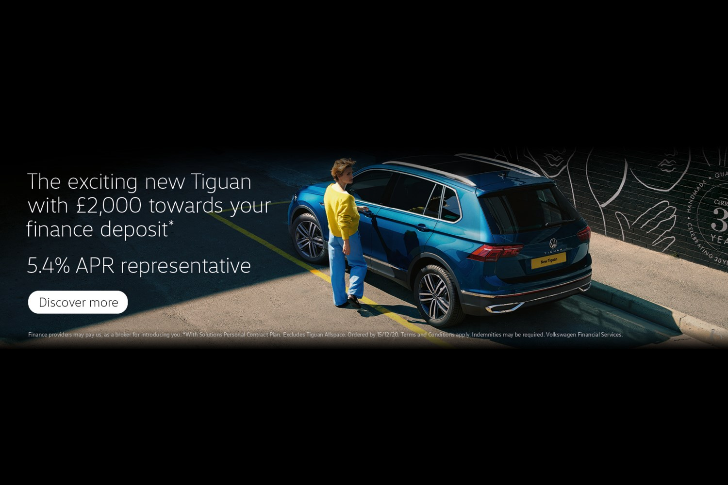 A bleu tiguan parked next to a kerb in a yellow marked parking bay. The wall bordering the pavement has hand prints on it and a women in a yellow top and blue trousers is going to open the car door